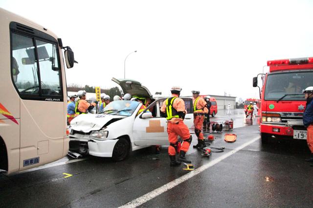 大型バスに追突した車両を解体し、けが人が救出する様子